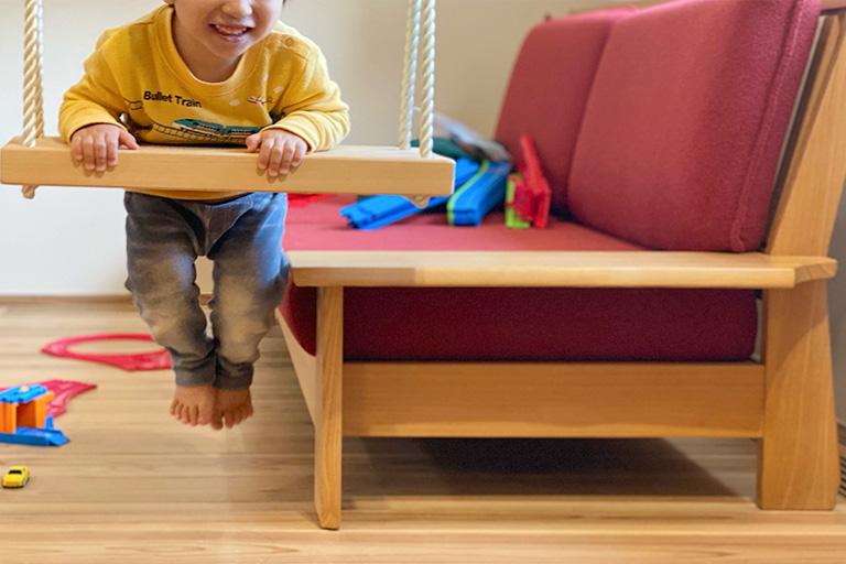 木製の屋内ブランコで遊ぶ子ども