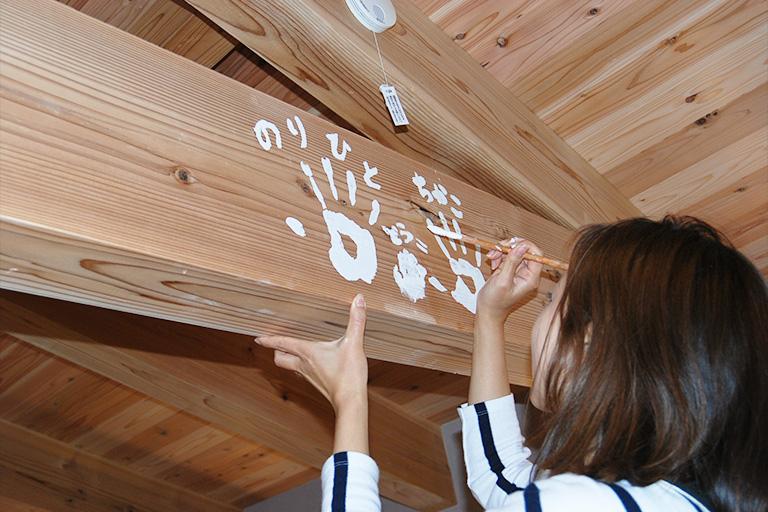 伐採した木を使用した家の梁に記念手形を残す