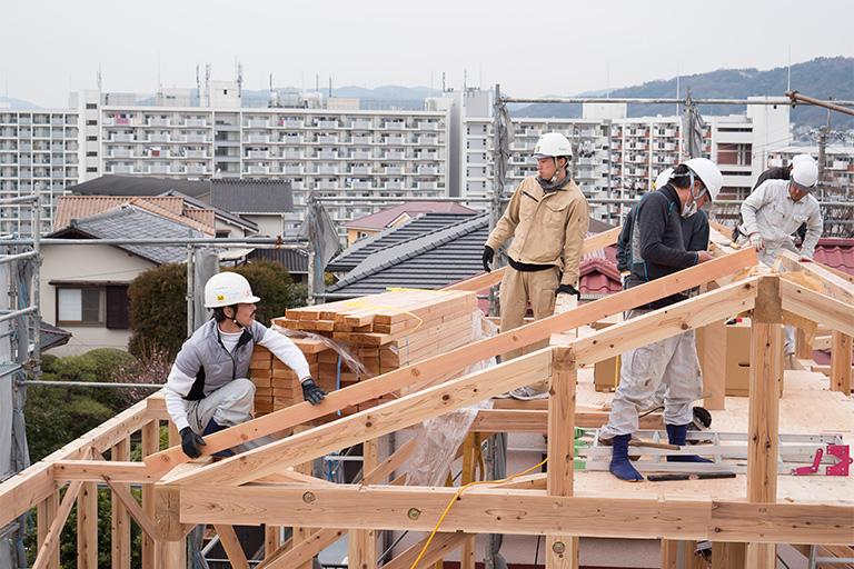 大工が家の骨組みを組み上げている様子